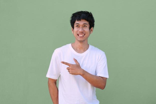 アジア人男性は、上面図と側面図を指している白いtシャツの笑顔を着ています。孤立したクリッピングパス画像。プロモーションとプレゼンテーション用の画像。