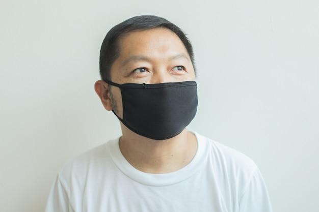 黒の医療マスクを身に着けているアジア人男性