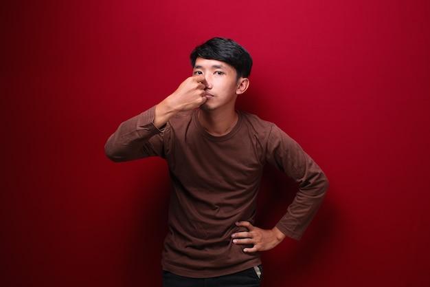 彼の鼻を覆う茶色のシャツを着ているアジア人男性