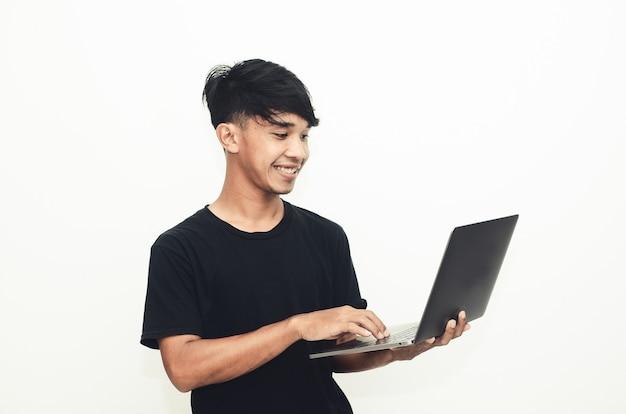 캐주얼한 검은 셔츠를 입고 웃는 표정으로 노트북을 들고 있는 아시아 남자