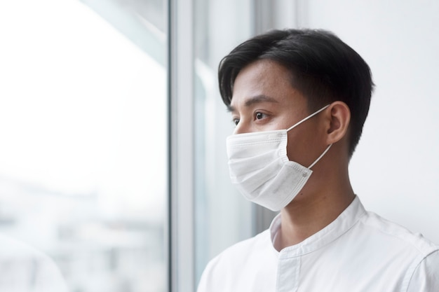 自宅でフェイスマスクを着用しているアジア人男性