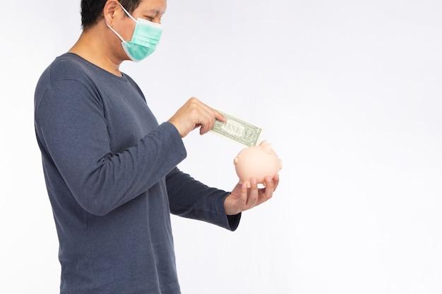 白い背景で隔離の紙幣とピンクの貯金箱を保持しているフェイスマスクを身に着けているアジア人男性