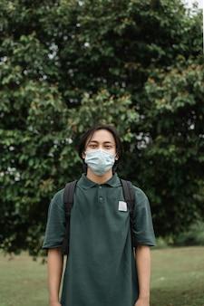 公園でマスクを着用して、covid19の蔓延を防ぐアジア人男性