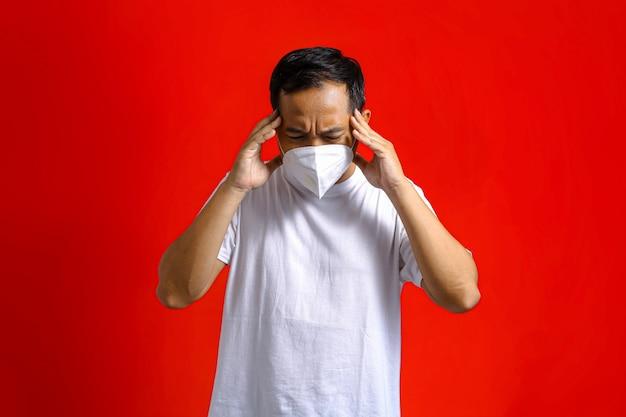두 손으로 머리를 잡고 두통이 있는 의료용 마스크를 쓴 아시아 남자