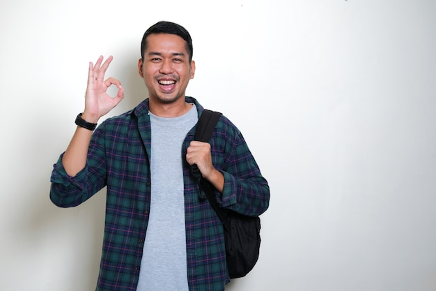 Азиатский мужчина в рюкзаке дает знак ок и показывает счастливое выражение лица