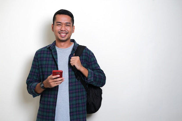 Азиатский мужчина в рюкзаке шилинг счастлив, держа свой мобильный телефон