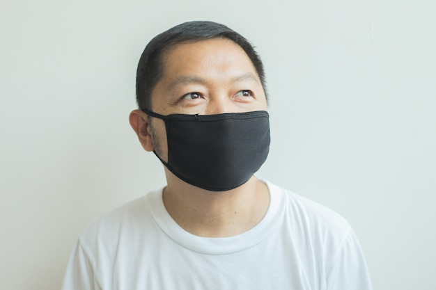 Asian man wearing a black medical mask