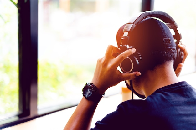 검은 셔츠를 입은 아시아 남성 프리랜서는 책상에서 일하고 헤드폰을 통해 음악을 들으면서 즐거운 시간을 보냅니다. 휴식 개념