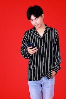 黒白のシャツを着て立っているアジア人の男性がカメラを見て左手をポケットジーンズに抱き、右手にスマートフォンを持って幸せそうな笑顔を見せ、赤い背景のスタジオで自信を持って撮影します。