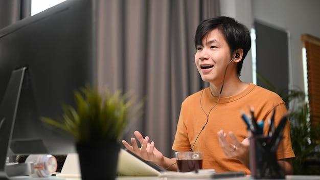 이어폰을 끼고 집에서 화상 회의를 하는 아시아 남자.