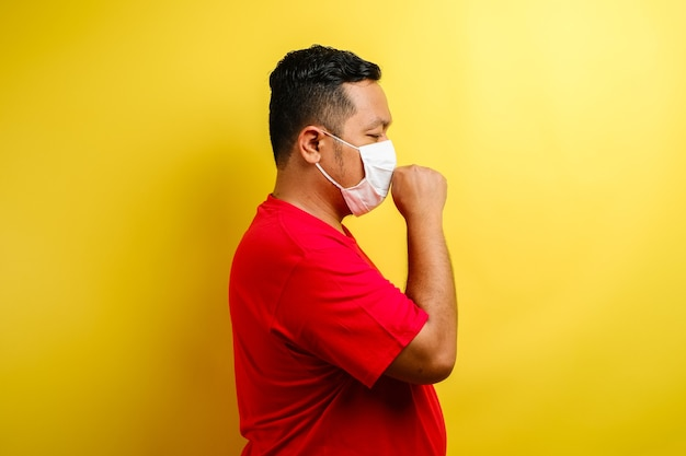 Asian man wearing fabric mask suffering from cough, isolated over yellow background