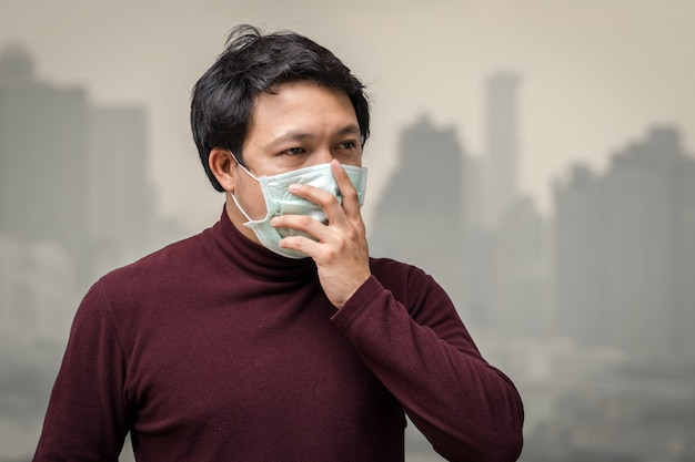 Asian man wearing the face mask against air pollution at the balcony of high apartment