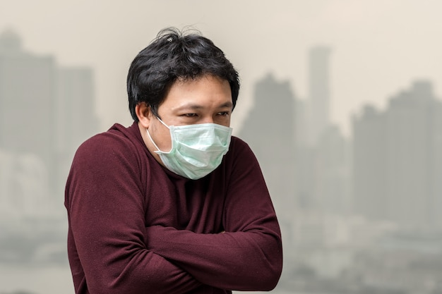 Asian man wearing the face mask against air pollution with cold at the balcony