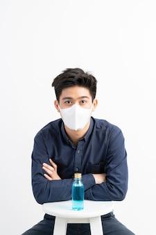 Uomo asiatico che indossa maschera facciale e alcool per lavarsi le mani per proteggere il coronavirus covid-19 nella stanza di quarantena