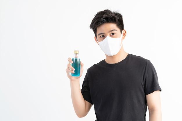 Азиатский мужчина в маске держит алкоголь для мытья рук для защиты от коронавируса covid-19 в карантинной комнате