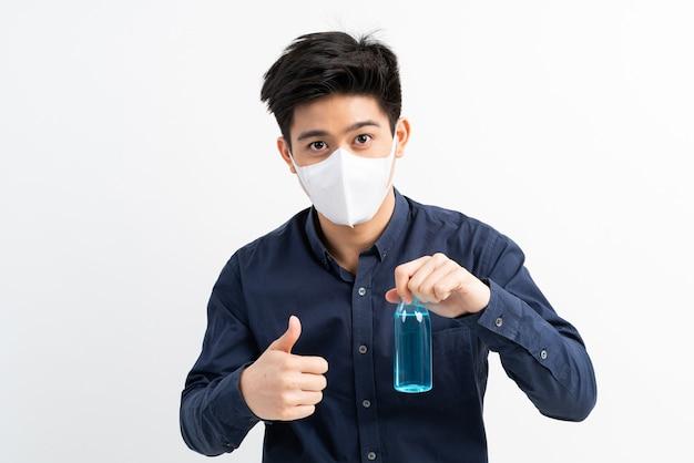 Uomo asiatico che indossa una maschera per il viso in possesso di alcol per lavarsi le mani per proteggere il coronavirus covid-19 nella stanza di quarantena