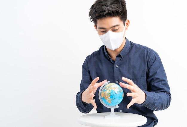 Азиатский мужчина в маске для лица, держа в руке карту мира, карта мира