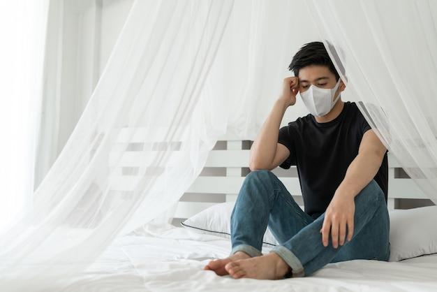Uomo asiatico che indossa la maschera per il viso per proteggere la sensazione di mal di testa e tosse a causa del coronavirus covid-19 nella stanza di quarantena