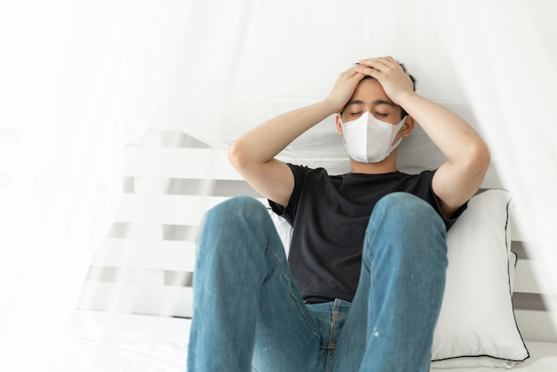 Asian man wearing face mask to protect  feeling sick headache and cough because of coronavirus covid-19 in quarantine room