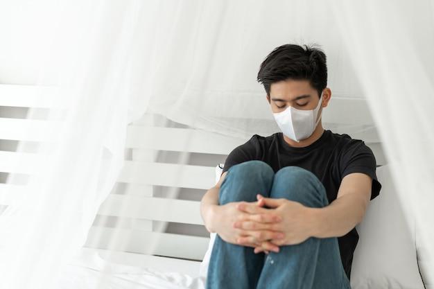 検疫室でコロナウイルスcovid-19のために気分が悪くなる頭痛と咳を保護するためにフェイスマスクを身に着けているアジア人男性