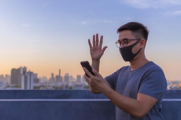 ウイルスから保護し、スマートフォンでビデオ通話をするためにフェイスマスクを身に着けているアジア人男性。