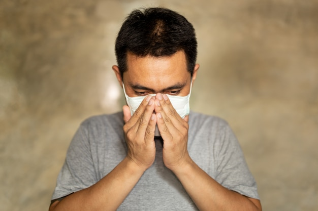 Asian man wearing a face mask with hand cover his mouth while coughing.