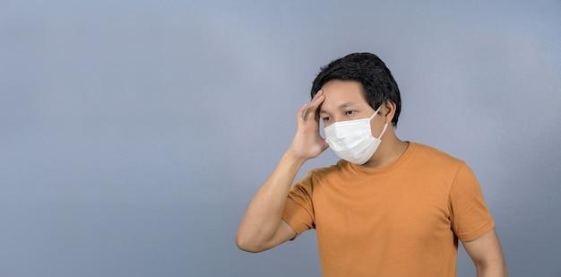 顔のサージカルマスクを身に着けているアジア人男性頭痛と青い背景の心配コロナウイルスパンデミック