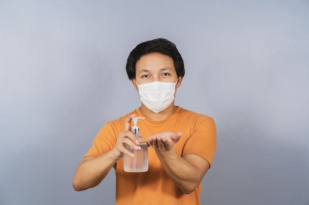Asian man wearing face surgical mask presenting and using alcohol gel or hand sanitizer