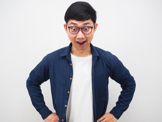 眼鏡をかけているアジア人男性は、白い背景を見下ろして驚いています