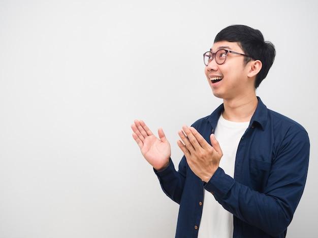 眼鏡をかけているアジア人男性が幸せを感じ、コピースペースを見て笑顔と手を表示します。