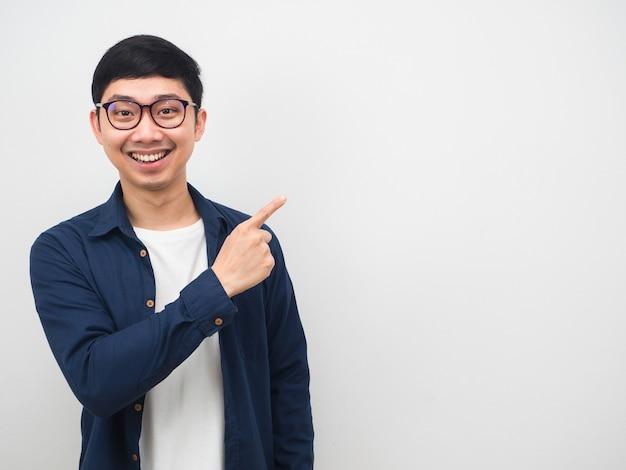 Азиатский мужчина в очках счастливая улыбка указывает пальцем на копию пространства на белом фоне