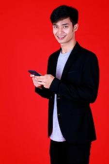 灰色のtシャツと黒のスーツを着て立っているアジア人の男性が手持ちのスマートフォンでカメラを見て幸せそうな笑顔を見て、赤い背景のスタジオで自信を持って撮影します。