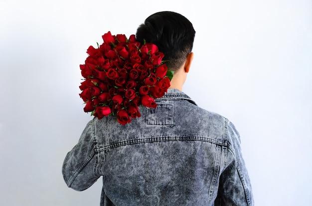 Азиатский мужчина в джинсовой куртке держит букет красных роз, изолированных на белом фоне для годовщины или концепции дня святого валентина.