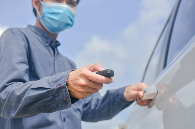 Asian man wearing medical mask and holding key to opening car door