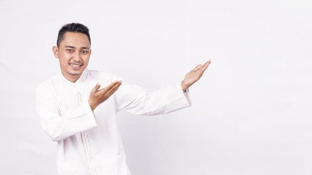 Азиатский мужчина в мусульманской одежде, указывая на пустой экран, изолированное белое пространство