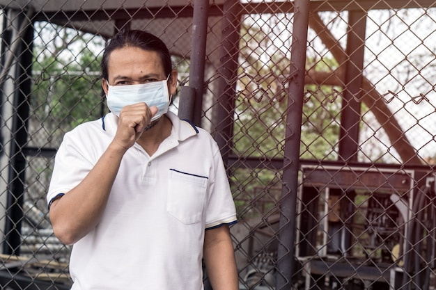 Asian man wearing mouth mask against air pollution.