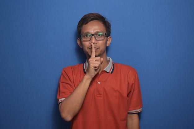 オレンジ色のカジュアルなtシャツを着たアジア人男性が唇に指で静かにすることを求める沈黙のコンセプト