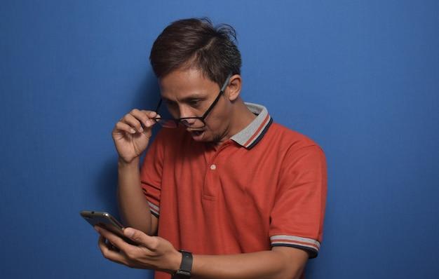 오렌지색 캐주얼 티셔츠를 입은 아시아 남성이 스마트폰에서 받은 좋은 소식에 놀라움을 금치 못했다
