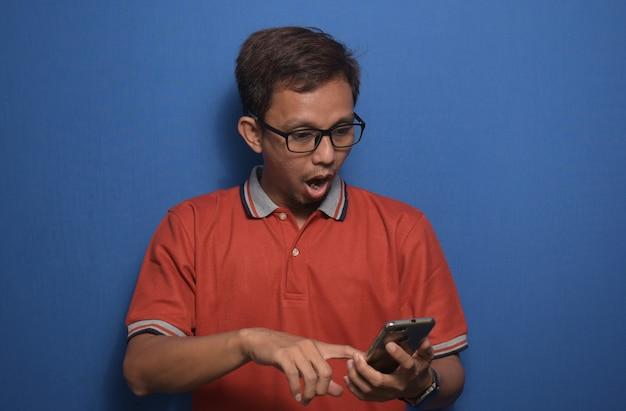 놀란 얼굴과 놀란 표정으로 스마트폰을 사용하여 주황색 캐주얼 티셔츠를 입은 아시아 남자