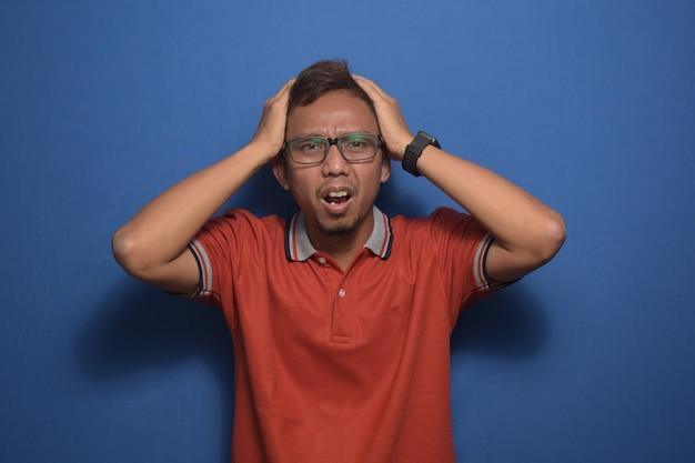 片頭痛に苦しんでいるストレスのために頭の頭痛に手でオレンジ色のカジュアルなtシャツを着ているアジア人男性