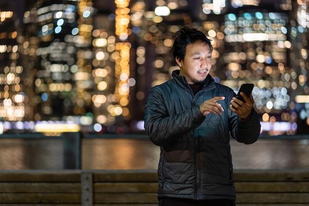 笑顔のアクションでスマート携帯電話を使用してオーバーコートスーツを着ているアジア人男性