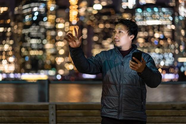 미소 행동으로 스마트 휴대 전화를 사용하여 외투 정장을 입고 아시아 남자