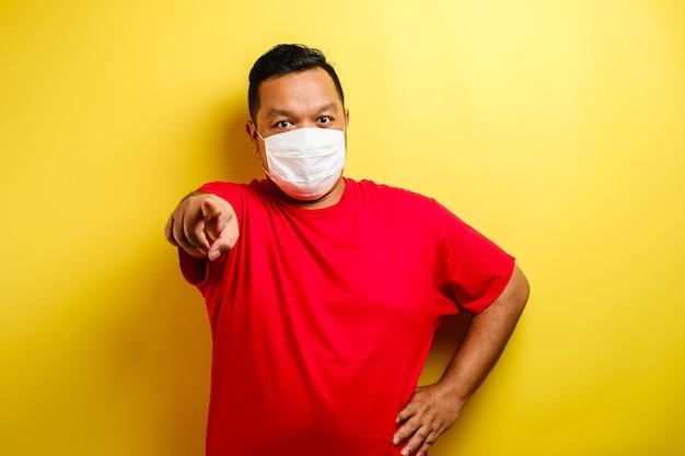 赤いtシャツと前向きのマスクを身に着けているアジア人の男性は、青い背景にマスクを着用する誰かを選択してカメラを見てください。