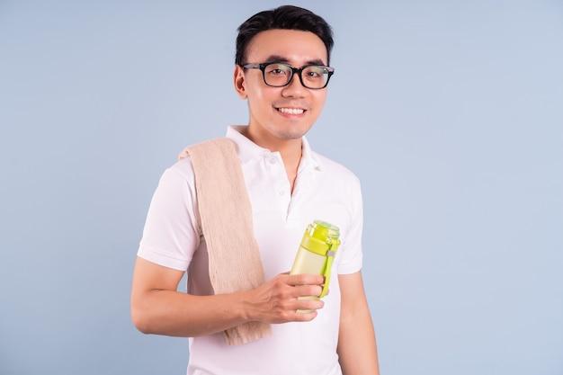 Азиатский мужчина в спортивной одежде и держит бутылку с водой, тренажерный зал и концепцию йоги