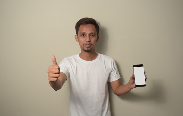 스마트폰을 들고 흰색 티셔츠를 입은 아시아 남성이 승인 표시를 하고 엄지손가락을 위로 올려