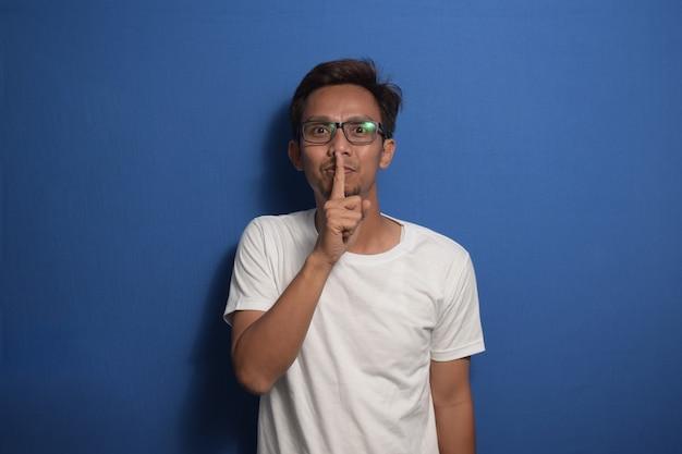 唇の沈黙と秘密の概念に指で静かにすることを求める白いtシャツを着ているアジア人男性