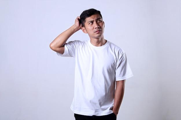 混乱した表情で白いtシャツを着ているアジア人男性白い背景で隔離