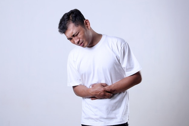 Asian man wearing white tshirt with stomachache expression isolated on a white background