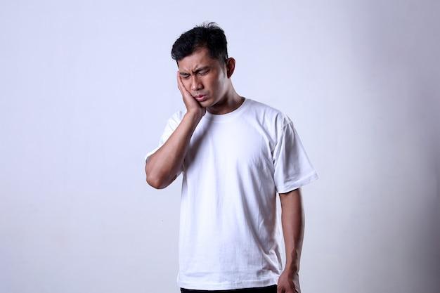 歯痛の表現と白いtシャツを着ているアジア人男性は白い背景で隔離