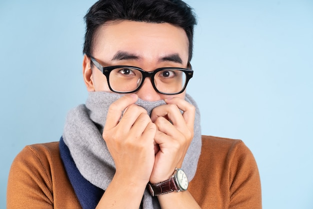 Asian man wearing winter clothes on blue background